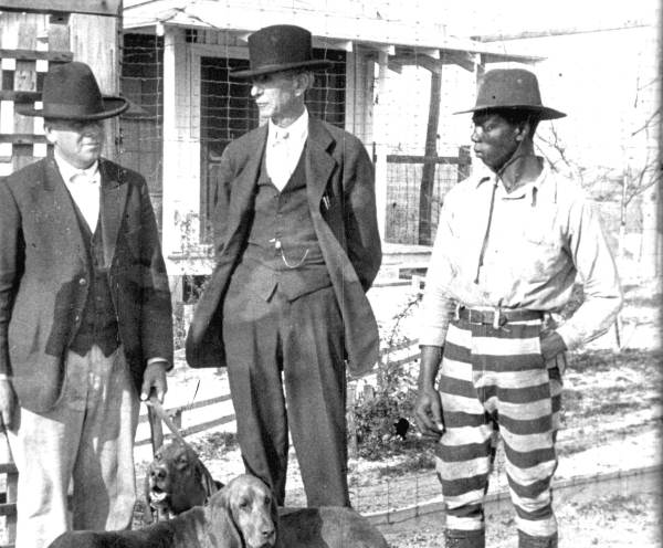 Florida farm prison inmate with other men and bloodhounds. 1927. Black & white photoprint, 8 x 10 in. State Archives of Florida, Florida Memory. , accessed 15 January 2019.
